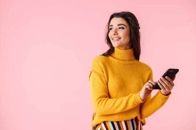 Piękna młoda kobieta ubrana w kolorowe ubrania stojących na białym tle nad różowym, przy użyciu telefonu komórkowego