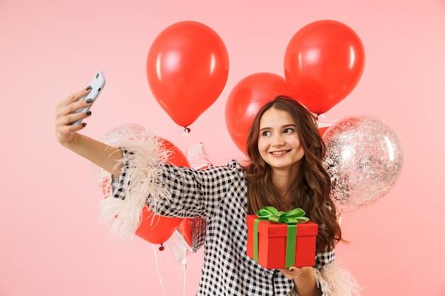 Piękna młoda kobieta ubrana w kurtkę stojącą na białym tle na różowym tle, obchodzi, trzymając kilka balonów, biorąc selfie