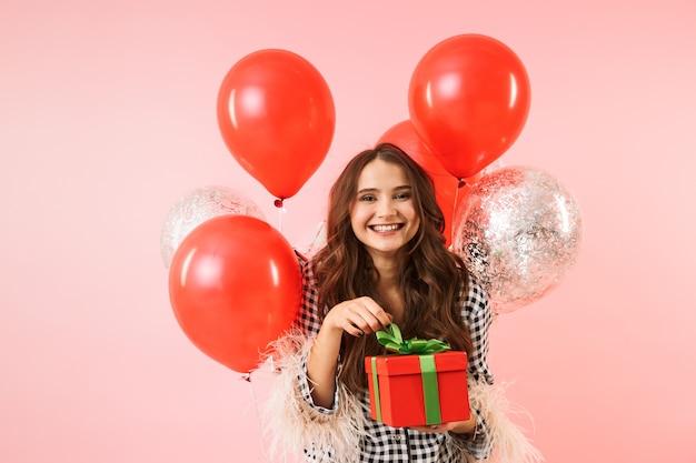 Piękna młoda kobieta ubrana w kurtkę stojącą na białym tle na różowym tle, obchodzi, trzymając kilka balonów i obecne pudełko