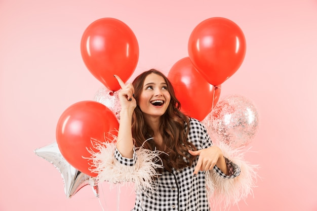 Piękna młoda kobieta ubrana w kurtkę stojącą na białym tle na różowym tle, świętuje, trzymając kilka balonów