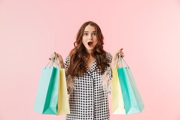 Piękna młoda kobieta ubrana w kurtkę stojącą na białym tle na różowym tle, trzymając torby na zakupy