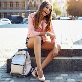 Piękna młoda kobieta ubrana w modne ciuchy, torebki, srebrne zegarki okulary przeciwsłoneczne siedzi w mieście. jasny makijaż, opalone ciało, długie nogi