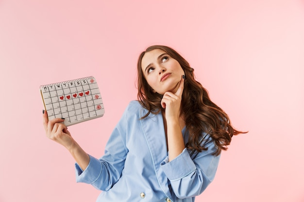 Piękna młoda kobieta ubrana w piżamę stojącą na białym tle na różowym tle, pokazując kalendarz menstruacyjny