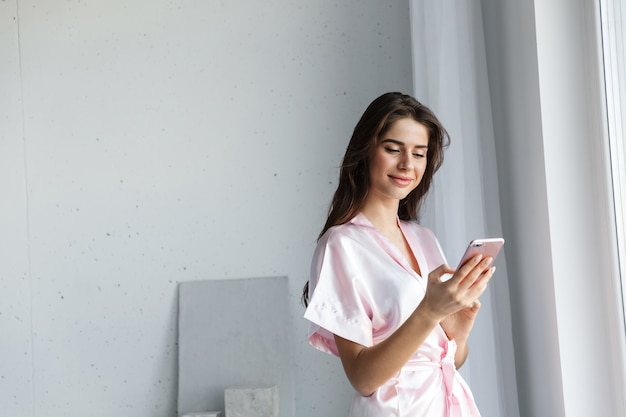 Piękna Młoda Kobieta Ubrana W Szlafrok Stojący Przy Oknie W Sypialni, Rozmawiając Przez Telefon Komórkowy Premium Zdjęcia