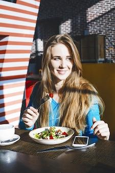 Piękna młoda kobieta udany modny i piękny telefon komórkowy i miskę sałatki w restauracji
