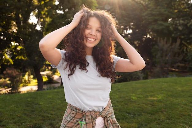 Piękna młoda kobieta uśmiecha się na zewnątrz
