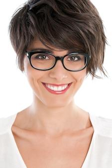Piękna młoda kobieta uśmiecha się z jej nową parę okularów na białym tle