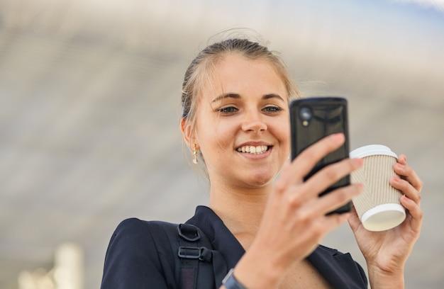 Piękna młoda kobieta używa aplikacji na swoim smartfonie, aby wysłać wiadomość tekstową
