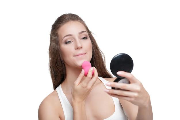 Piękna młoda kobieta używa blendera kosmetycznego do nakładania podkładu do makijażu na twarzy na białym tle