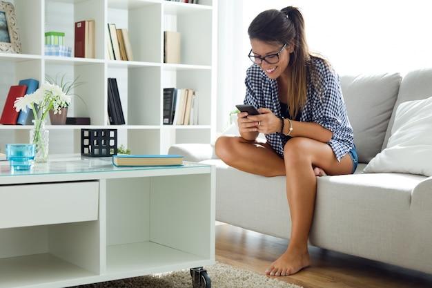 Piękna młoda kobieta używa jej telefon komórkowego w domu.