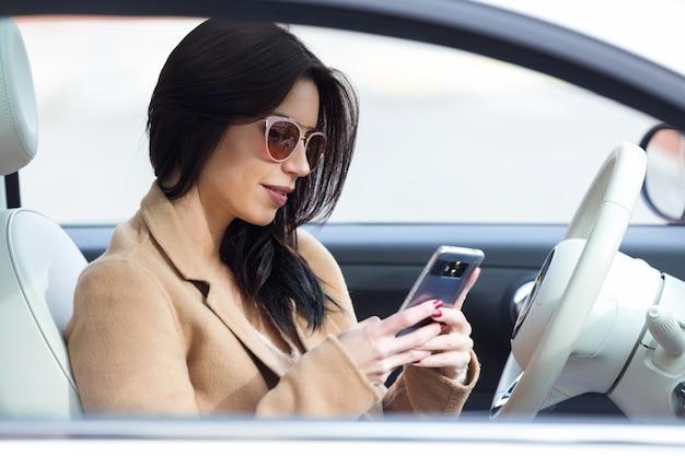 Piękna młoda kobieta używa jej telefon komórkowego w samochodzie.