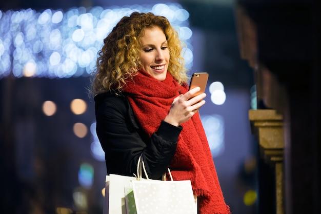 Piękna młoda kobieta używa jej telefon komórkowego w ulicie przy nocą.