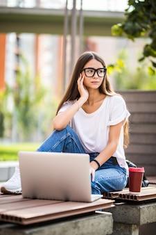 Piękna młoda kobieta używa laptop podczas gdy siedzący na ławce, pije takeaway filiżankę