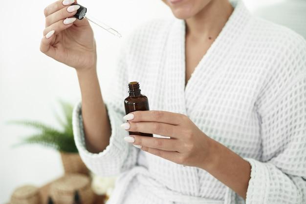 Piękna młoda kobieta używa na dłonie nawilżającego serum przeciwdziałającego efektom starzenia. uroda pielęgnacja skóry ciała i kosmetyki zastosuj koncepcję.