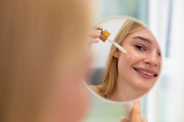 Piękna młoda kobieta używa olejku do pielęgnacji twarzy