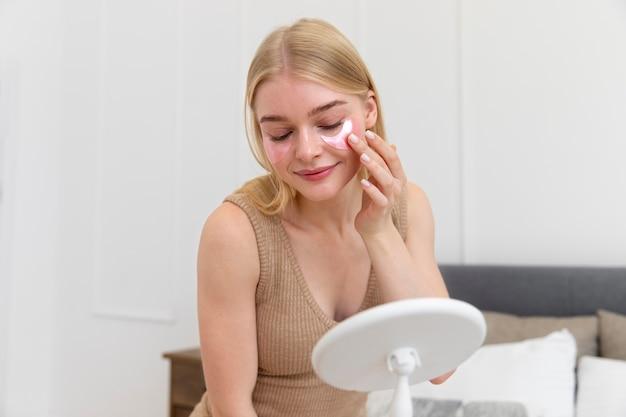Piękna młoda kobieta używa produktu do pielęgnacji twarzy