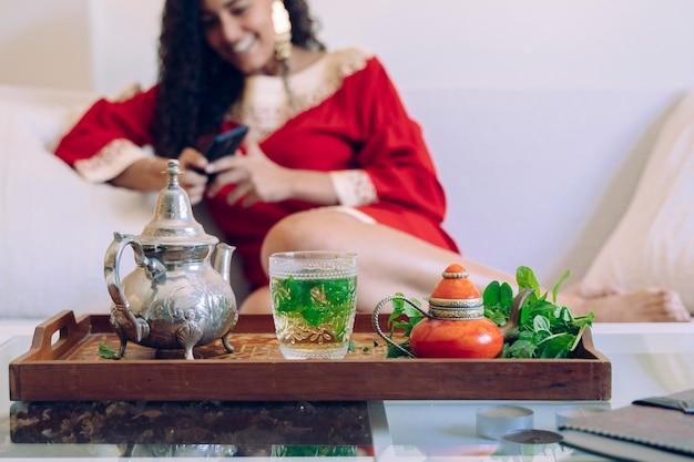 Piękna młoda kobieta używa smartphone w domu i pijący herbaty