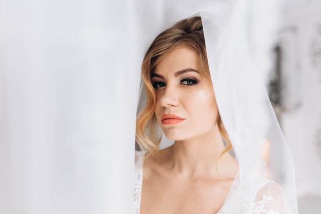 Piękna młoda kobieta w białej bielizny pozuje w biały jedwabny szlafrok w jasny pokój hotelowy