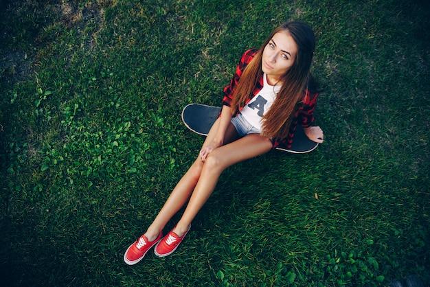Piękna młoda kobieta w białej koszulce, czerwonej koszulce, szortach i trampkach, siedząc na deskorolce na trawie