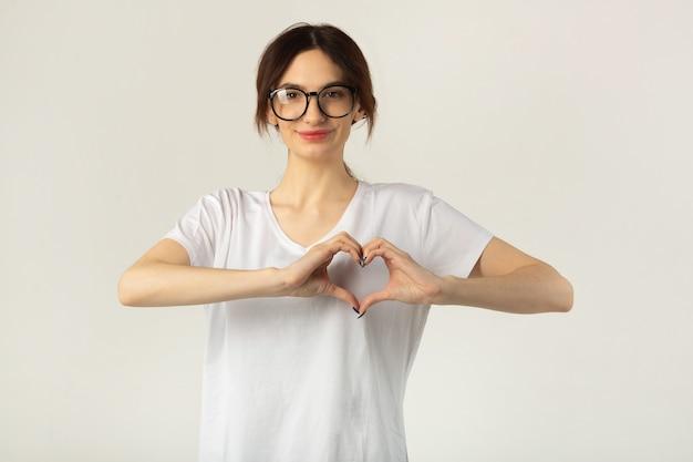 Piękna młoda kobieta w białej koszulce na białym tle z gestem ręki