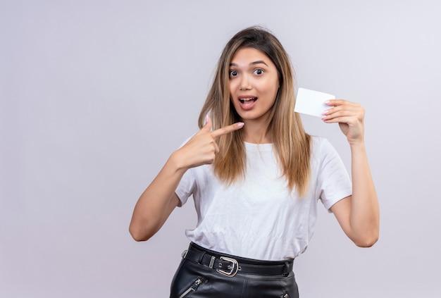 Piękna młoda kobieta w białej koszulce, wskazując na notatkę