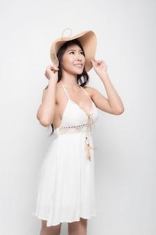 Piękna młoda kobieta w białej letniej sukience i kapeluszu przeciwsłonecznym stoi, odwracając wzrok i uśmiechając się na białym tle na białej powierzchni