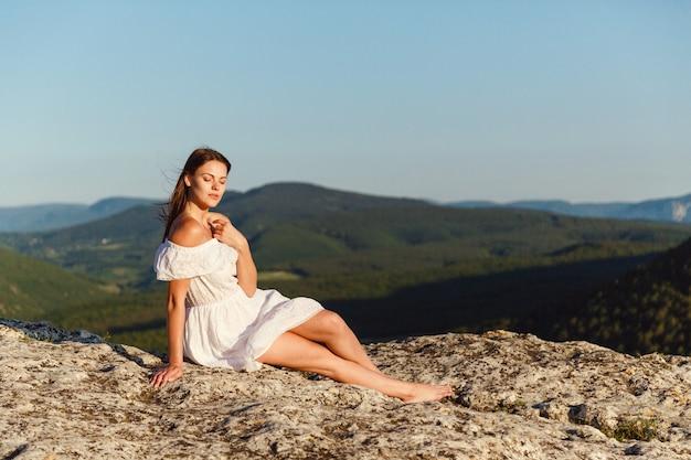 Piękna młoda kobieta w białej sukni cieszy się przepiękną scenerią w górach podczas zachodu słońca