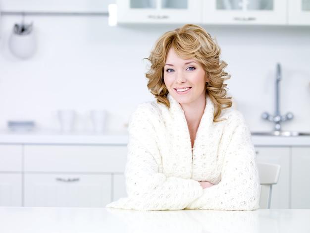 Piękna młoda kobieta w białej sukni domowej siedzi w kuchni