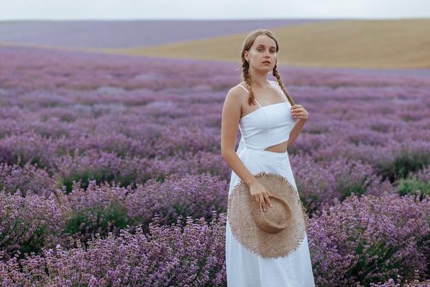 Piękna młoda kobieta w białej sukni i kapeluszu idzie przez lawendowe pole