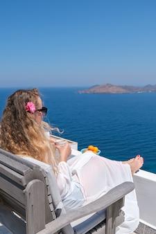 Piękna młoda kobieta w białej sukni kwiat we włosach i filiżance kawy siedząc na białym tarasie balkon domu lub hotelu z widokiem na morze.