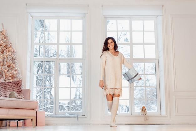 Piękna młoda kobieta w białej sukni pozuje z prezenta pudełkiem