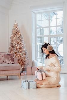 Piękna młoda kobieta w białej sukni pozuje z prezentów pudełkami