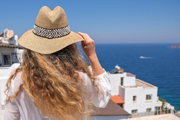 Piękna młoda kobieta w białej sukni słomkowy kapelusz na białym tarasie balkonie domu lub hotelu z widokiem na morze.