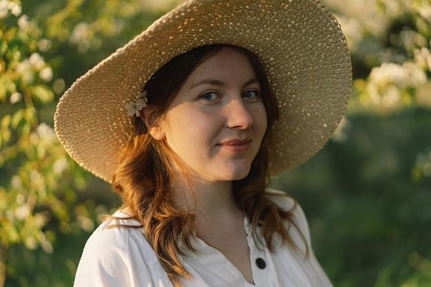 Piękna młoda kobieta w białej sukni spaceruje po wiosennym ogrodzie