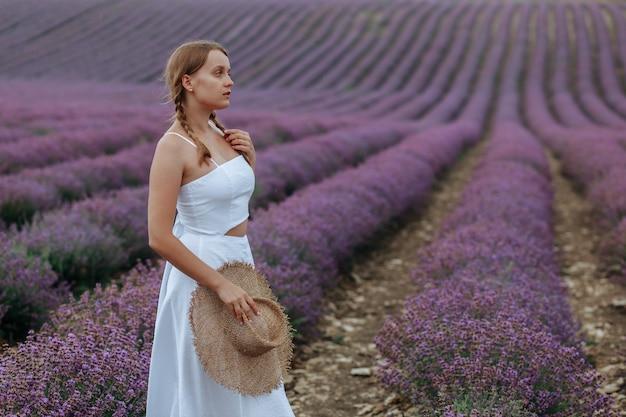 Piękna młoda kobieta w białej sukni z kapeluszem spaceruje po lawendowym polu