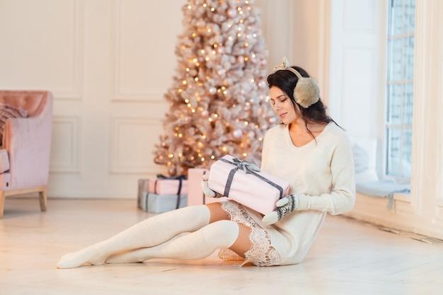Piękna młoda kobieta w białej sukni z prezentami w ich rękach