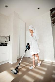 Piękna młoda kobieta w białej szacie zajmuje się sprzątaniem domu odkurzaczem