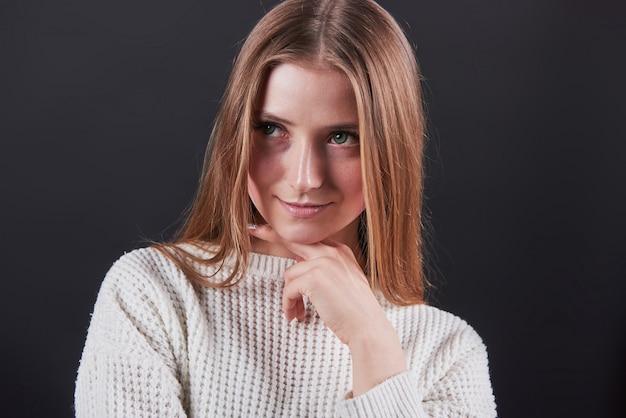 Piękna młoda kobieta w białym swetrze i dżinsach odizolowywających na czarnym tle