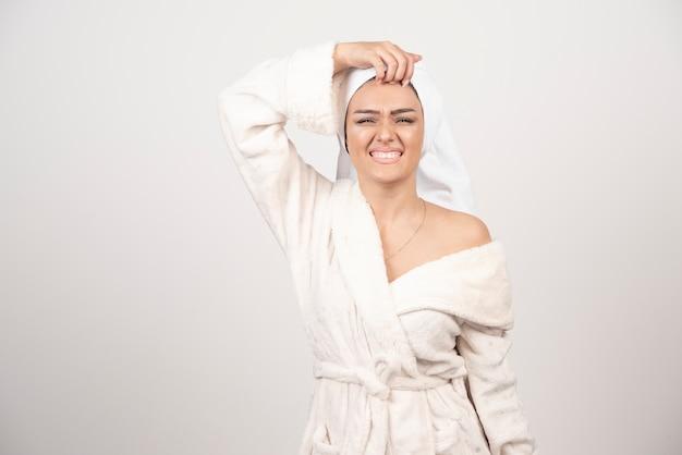 Piękna młoda kobieta w białym szlafroku na białym tle na białej przestrzeni