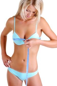Piękna młoda kobieta w bieliźnie o smukłym ciele zdrowia mierzy piersi. widok z przodu nad białą przestrzenią.