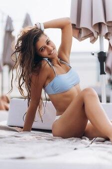 Piękna młoda kobieta w bikini, odpoczynek na świeżym powietrzu przy basenie