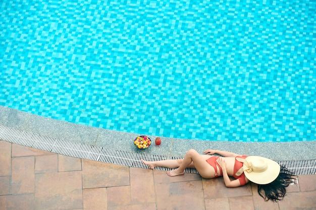 Piękna młoda kobieta w bikini zakrywająca twarz słomkowym kapeluszem podczas opalania przy basenie