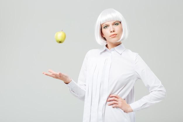 Piękna młoda kobieta w blond peruce stojąca i rzucająca jabłkiem w powietrze