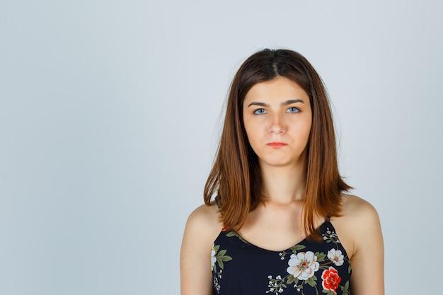 Piękna młoda kobieta w bluzce i wyglądająca na sfrustrowaną