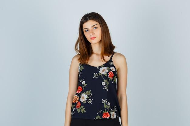 Piękna młoda kobieta w bluzce i wyglądająca rozsądnie