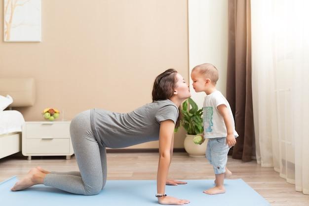 Piękna młoda kobieta w ciąży i mały chłopiec uśmiechający się leżąc na macie do jogi
