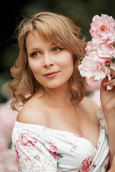 Piękna młoda kobieta w ciąży idzie w ogrodzie różanym. portret kobiety w ciąży w sukience. lato.