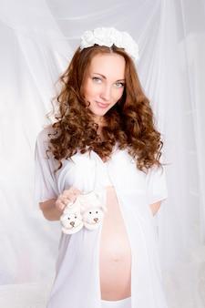 Piękna młoda kobieta w ciąży, nastolatek w białej bieliźnie z butami dziecka