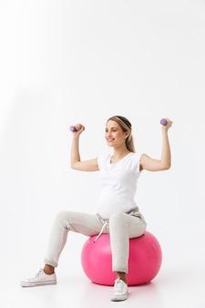 Piękna młoda kobieta w ciąży robi ćwiczenia sportowe z piłką fitness na białym tle na białym tle