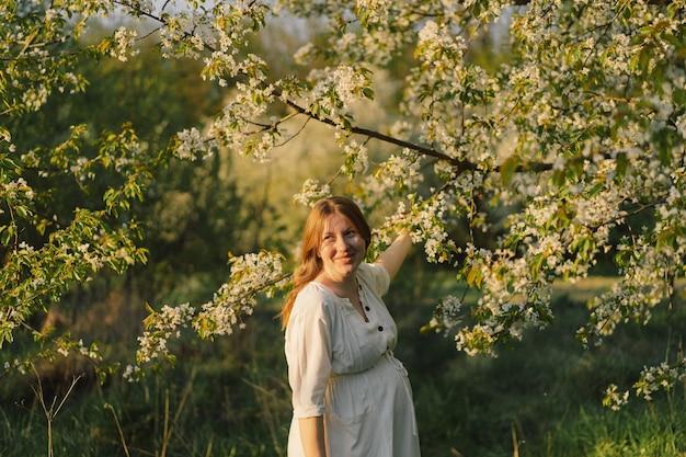 Piękna młoda kobieta w ciąży w białej sukni spaceruje po wiosennym ogrodzie